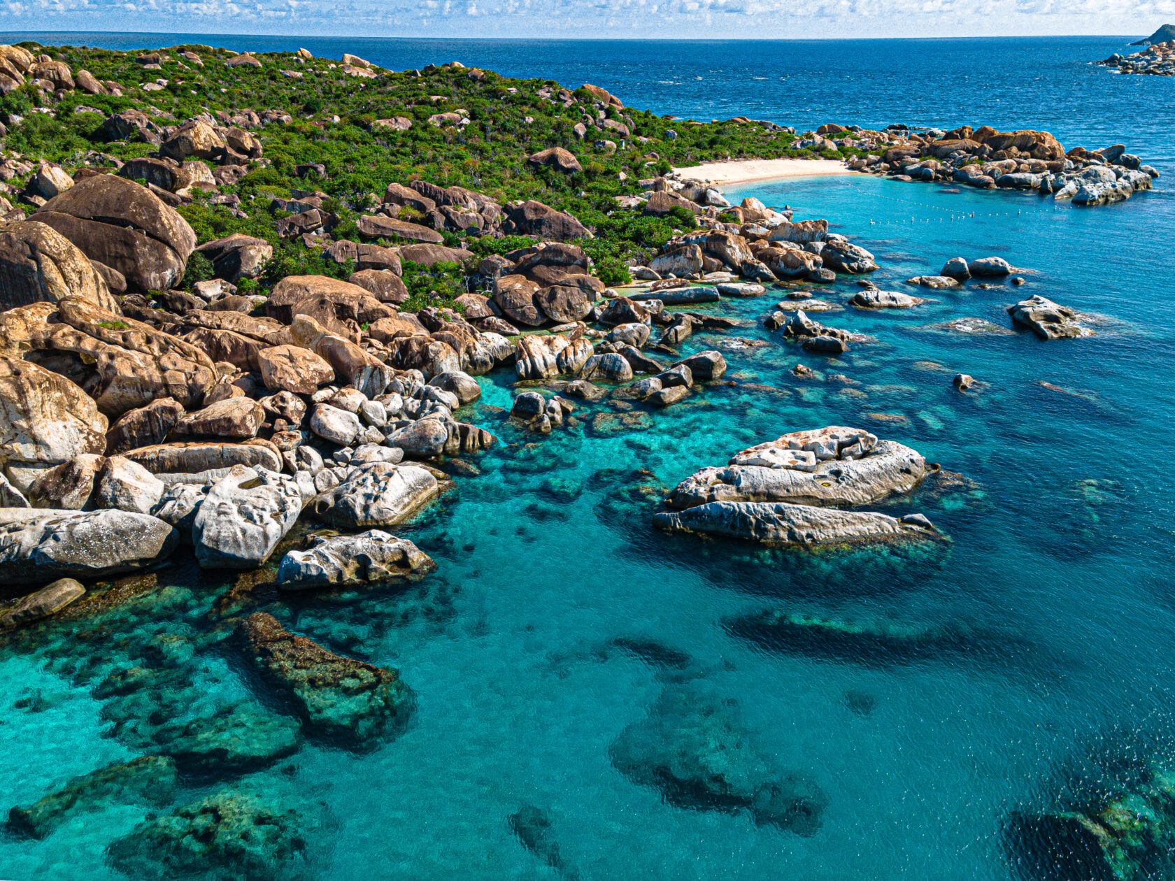 Secluded beach with rocks and clear blue water
